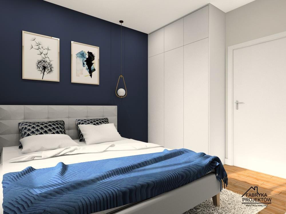 Sypialnia, granatowa ściana za łózkiem, biała szafa, szare łóżko