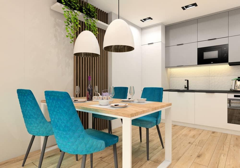 Stół pomiędzy kuchnią a salonem, białe lampy, turkusowe krzesła, kuchnia szara, biała, mała, drewno na ścianie