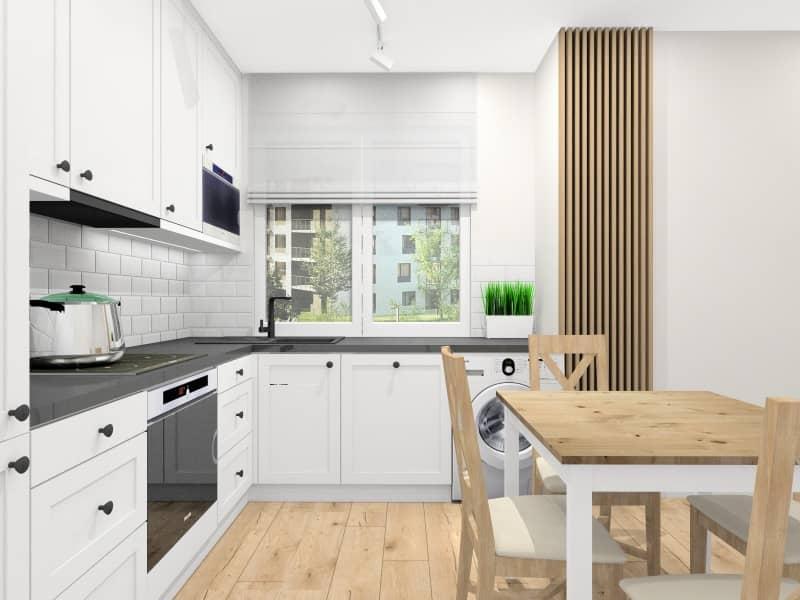 Kuchnia, wystrój skandynawski, białe fronty MDF, czarny blat kamień, jedno okno w kuchni, lamele na ścianie, stół biały, drewniany, płytki imitujące cegłe na ścianie, uchwyty czarne