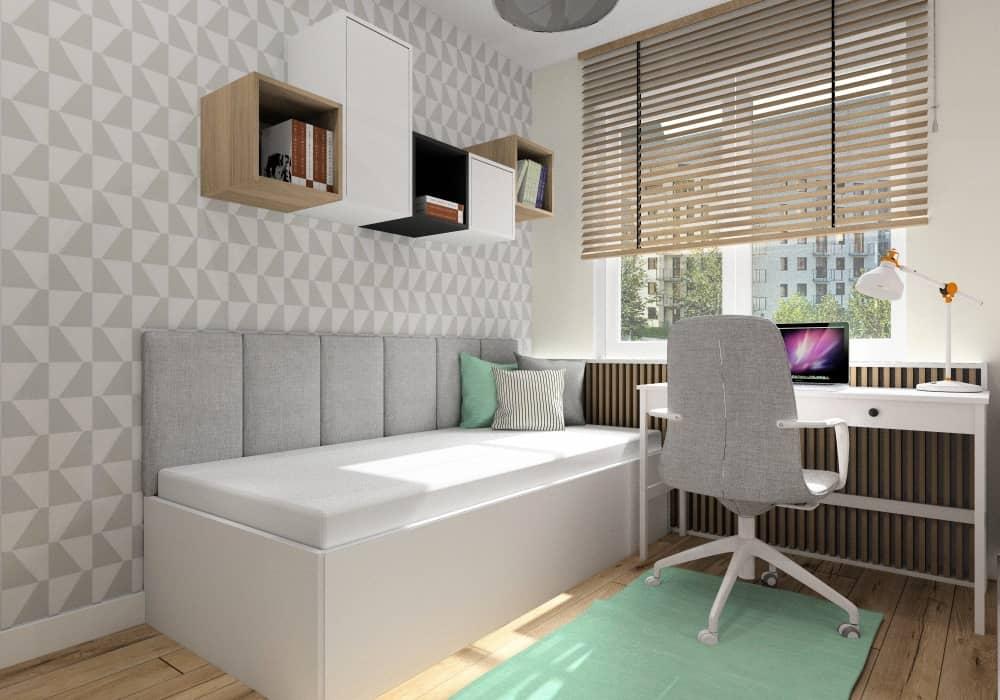 Pokój młodzieżowy dla nastolatki w bloku, widok na białe biurko pod oknem, ściana z łózkiem, szara tapeta w trójkąty, łózko z zagłówkiem tapicerowanym, miętowy dywan, miętowe poduszki, szare poduszki