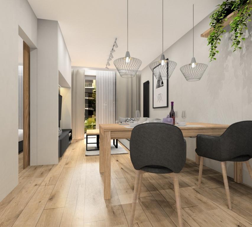 Salon, projekt mieszkania 43m2, mieszkanie dwupokojowe, zabudowa RTV w kolorze białym, drewno ciepły odcień, grafitowy, beżowo-szara sofa, białe lampy, plakat nad sofą złoty, czarny, stolik kawowy drewniany