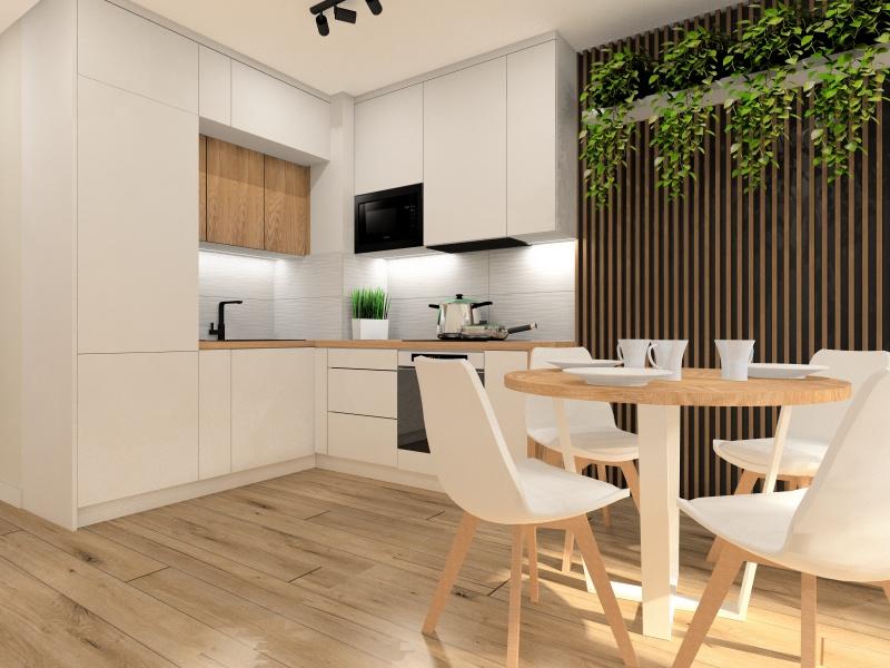 Salon z aneksem, małe mieszkanie 37 m2, meble kuchenne białe, blat drewniany, kwiaty na ścianie, stół okrągły z drewnianym blatem, podłoga drewniana