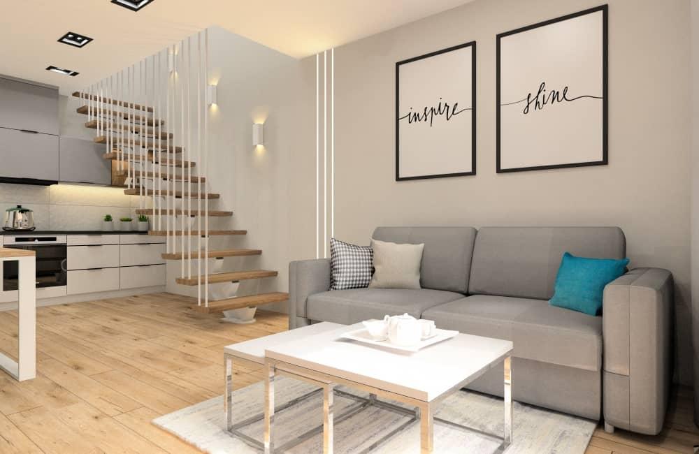 Wnętrze salonu z anekem kuchennym, schody w salonie, plakaty nad sofą, czarne, białe, drewno, turkus
