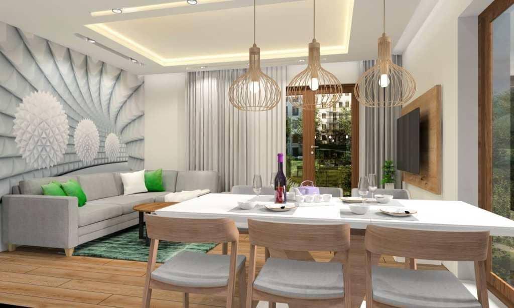 Salon, kuchnia dodatki: Fototapeta na ścianie za sofą narożną, dywan zielony, poduszki zielone, poduszki białe, lamy azurowe drewniane, drewno na ścianie za TV, podświetlane półki z wnękami