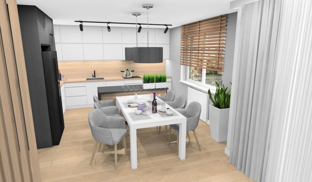 Salon z kuchnia, widok na kuchnię średniej wielkości, zabudowa kuchni w kształcie litery L, wyspa pośrodku, stół biały, frontu kuchenne białe, szarek, blat drewniany