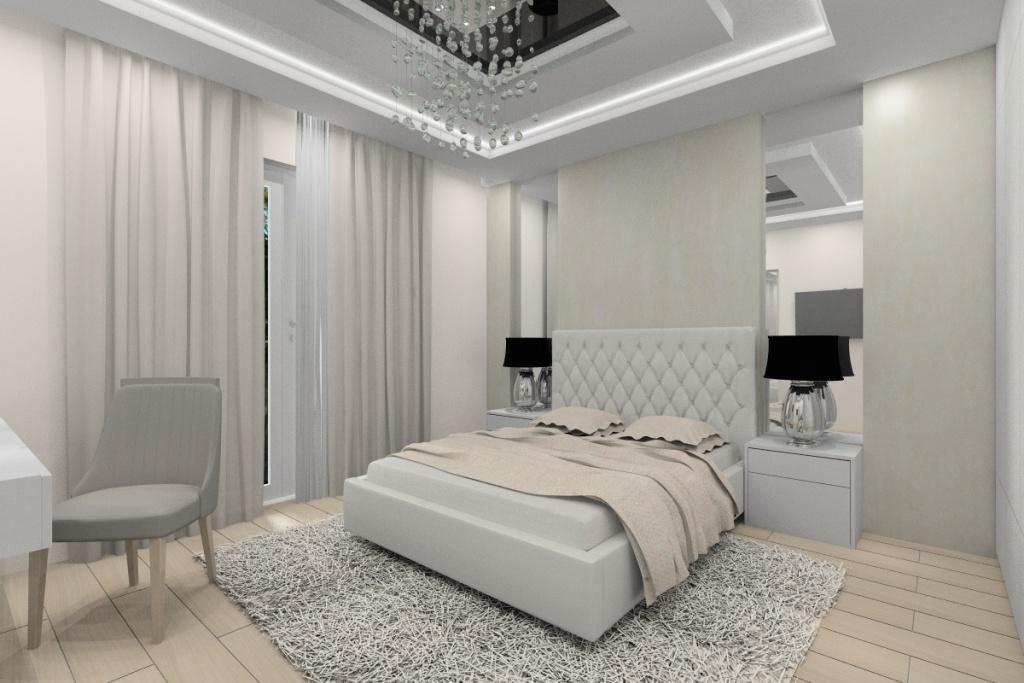 Sypialnia urządzona w stylu glamour, łóżko z pikowanym zagłówkiem, szafki nocne, toaletka z lustrem, podwieszany sufit, żyrandol glamour, lustra w sypialni, dywan, beż, biały