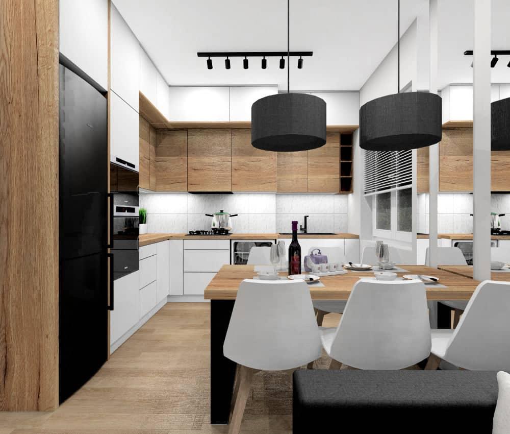 Salon z aneksem w małym mieszkaniu, meble kuchenne w kształcie litery L, zabudowa meblowa w kolorze białym i drewno, szafki kuchenne do sufitu