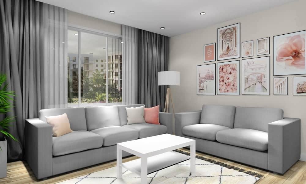 Salon z kuchnią, Nowoczesna aranżacja wnętrz, dywan beżowy geometryczny, dwie sofy, stolik kawowy biały, plakaty pudrowy róż